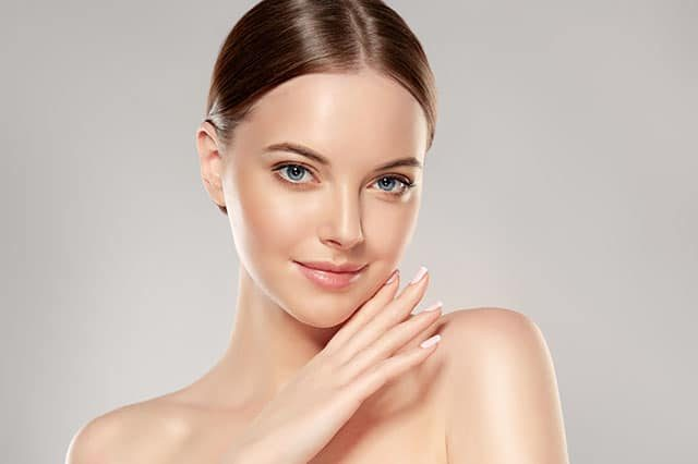 Beautiful Young Woman with Clean Fresh Skin touch own face . Fac