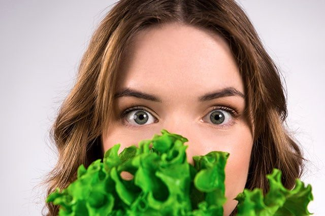 Young girl hiding behind lettuce leaves.